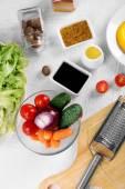 Kuchyňské potřeby a suroviny na salát na stole, na světlé pozadí