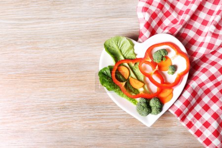 Photo for Useful cut vegetables on a plate in the form of heart on wooden table top view - Royalty Free Image
