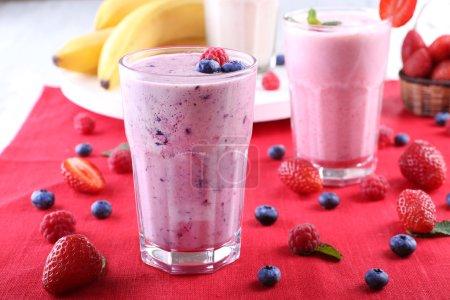 Milkshakes with berries at red textile