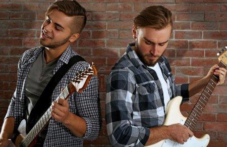 Young men playing guitars