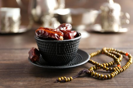 Dates fruit and rosary on served wooden background, close up