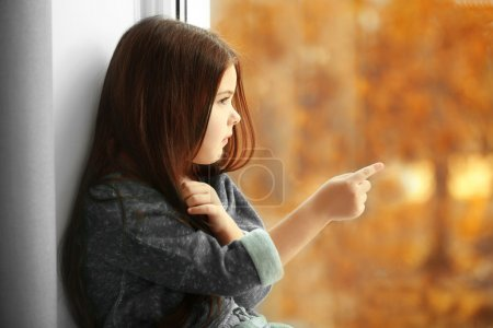 Photo pour Petite fille attendant quelqu'un et regardant par la fenêtre - image libre de droit