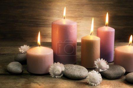 Photo pour Sertie de bougies, de galets et de fleurs sur fond en bois de Spa - image libre de droit