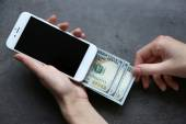 Hands holding smart phone with dollar banknotes on grey background. Making money online