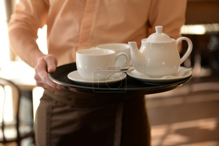 Waiter holding tray with teapot and cups close up