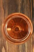Sklenka vína na dřevěný stůl. Pohled shora