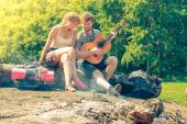 Young couple of tourists playing guitar