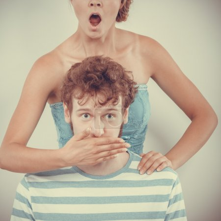 surprised couple wide eyed girl covering mouth her man