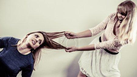 Photo pour Des femmes folles agressives qui se battent en tirant les cheveux. Deux jeunes filles qui luttent pour gagner une bagarre. Violence . - image libre de droit