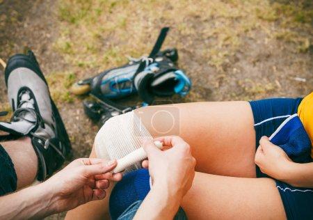 Photo pour Blessures de sport. Couple de patineurs en plein air. Jeune femme souffrant de douleurs dans les jambes après une chute sur le bitume, l'homme contribue à son genou blessé le pansement - image libre de droit