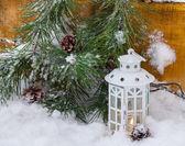 Dekorativní svítilna pálení na sněhu s větví jehličnanů