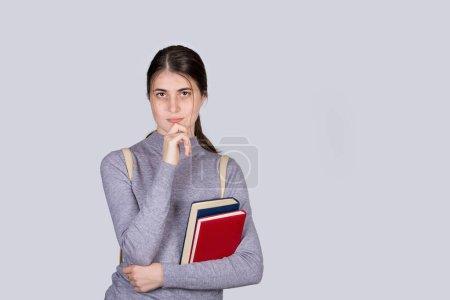 Photo pour Portrait étudiant réfléchi de fille tenant des manuels regardant perplexe, main sous le menton, isolé sur fond blanc. Étudiante sérieuse préparée pour les examens, la pensée des ides et la planification. - image libre de droit