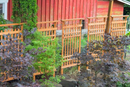 Wood Trellis Covering Red Barn Fencing