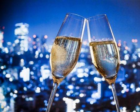 Photo pour Flûtes à champagne avec des bulles d'or font acclamations sur fond bleu lumières de la ville avec de l'espace pour le texte - image libre de droit