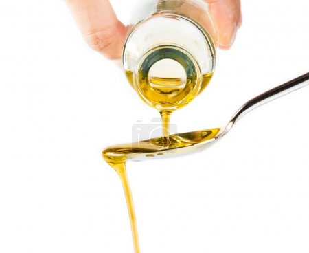 Bottle of extra virgin olive oil pouring over a spoon isolated on white background