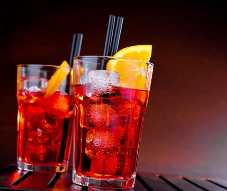 Photo for Spritz aperitif aperol cocktail with orange slices and ice cubes on wood table and color gradient background - Royalty Free Image