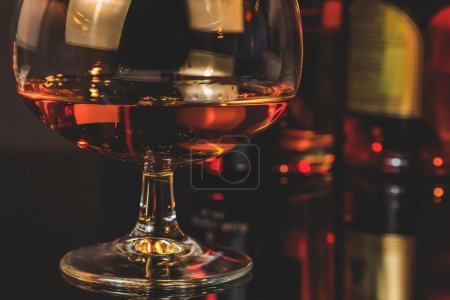 Photo for Snifter of brandy in elegant typical cognac glass  in front of bottles in background, warm atmosphere - Royalty Free Image