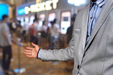 Photo pour Business Man spectacle accueillir ou inviter geste sur Movie Ticket System Contexte comme divertissement d'affaires ou concept complexe de cinéma de théâtre. - image libre de droit