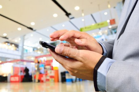 Business Man using Mobile Phone in Modern Shopping Mall