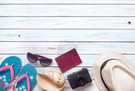 Photo pour Pose plate d'articles de vacances, y compris lunettes de soleil, tongs, chapeau, montre, appareil photo et passeport sur des planches de bois blanc - image libre de droit