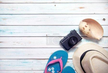 Foto de Lay Flat de artículos de vacaciones, incluyendo gafas de sol, sandalias, sombrero, reloj, cámara y pasaporte en tablones de madera blancos - Imagen libre de derechos