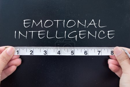 Photo for Hands holding a tape measuring the words emotional intelligence - Royalty Free Image