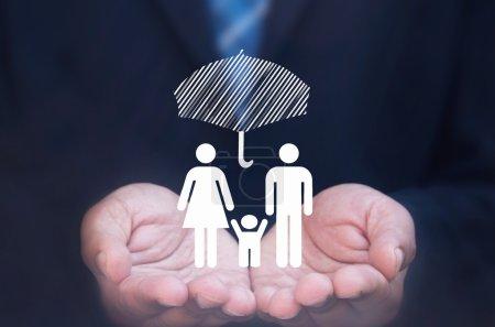 Photo pour Homme d'affaires tenant une icône familiale protégée par un parapluie - image libre de droit