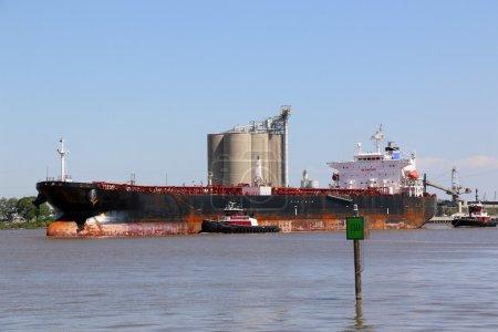 Photo pour Super navire-citerne entrant au port pour livrer des milliers de gallons de pétrole brut, deux remorqueurs donnent le navire . - image libre de droit