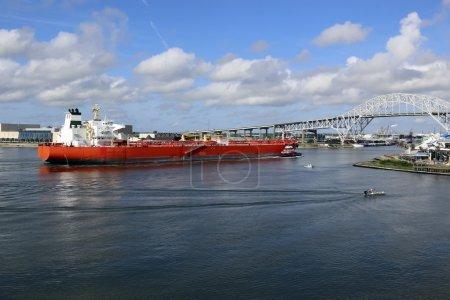 Photo pour Grand navire entrant dans le port pour livrer des marchandises, remorqueur guidant le navire pour le garder sur le chemin, plusieurs petits bateaux à proximité - image libre de droit