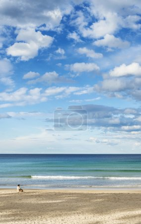 Photo for Solitary lonely woman on empty manly beach north sydney australia - Royalty Free Image