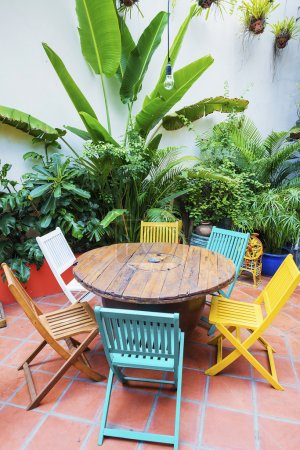 brightly coloured wooden chairs and table in garden