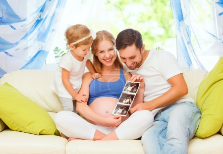 Happy family waiting for baby looking ultrasound pregnant mom, d