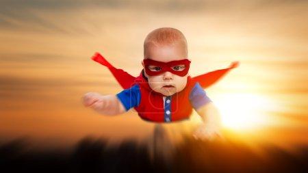 Photo pour Tout-petit petit bébé superman super héros avec une cape rouge volant dans le ciel - image libre de droit