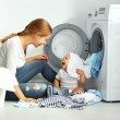 Mother a housewife with a baby engaged in laundry ...