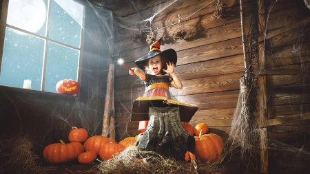 Halloween. child little witch with magic wand and reading a mag