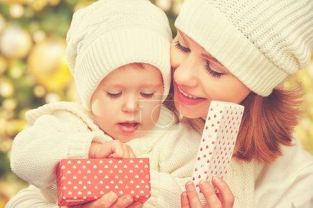 Photo pour Heureuse mère de famille et fille dans des chapeaux blancs avec cadeau de Noël en hiver - image libre de droit