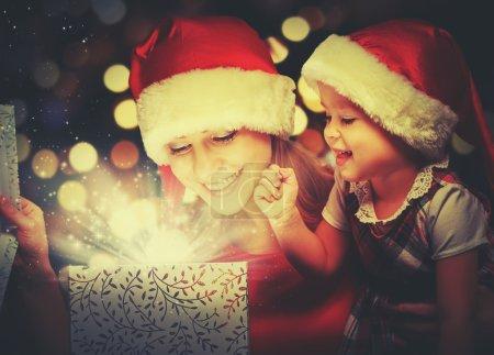 Photo pour Boîte cadeau magique de Noël et une femme heureuse famille mère et fille bébé fille - image libre de droit