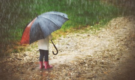 happy baby girl with  umbrella in the rain runs through