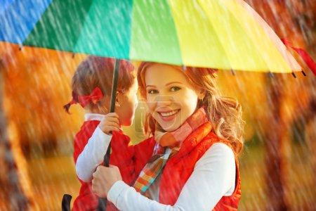 Photo pour Heureuse famille maman et enfant fille avec le parapluie couleur arc-en-ciel sous la pluie sur la nature - image libre de droit