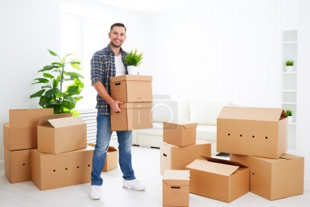 Photo for Moving to a new apartment. Young happy man with cardboard boxes - Royalty Free Image