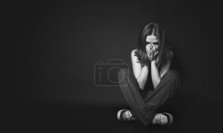 woman in depression and despair crying on black dark
