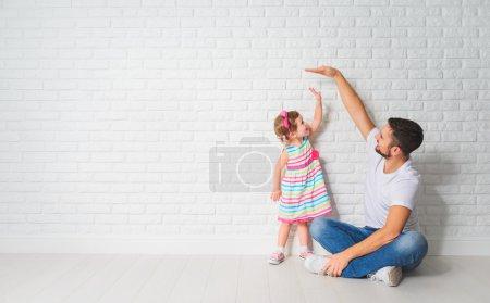 Photo pour Concept. Papa mesure la croissance de son enfant fille à un mur de briques vierges - image libre de droit