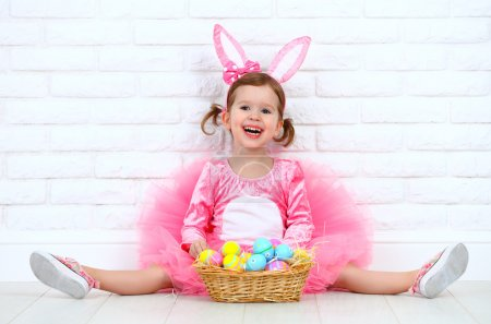 Happy child girl in a costume Easter bunny rabbit with basket of
