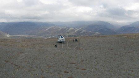 Photo pour Vue aérienne d'un hélicoptère et d'un groupe de randonneurs sur un sommet de montagne. Clip. Concept d'aventure et de tourisme, les gens explorent la région montagneuse naturelle sauvage - image libre de droit
