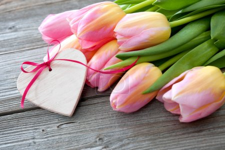 Colorful tulips and heart on wooden background