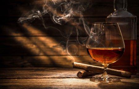 Photo pour Verre de whisky avec cigare fumant et glaçons sur table en bois - image libre de droit