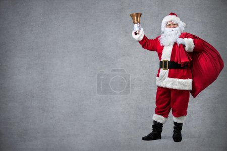 Photo for Santa Claus with sack of gifts, ringing in a bell - Royalty Free Image
