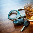 Whiskey with car keys and handcuffs concept for dr...