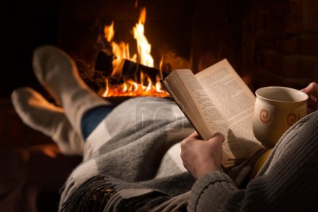 Photo for Woman resting with cup of hot drink and book near fireplace - Royalty Free Image