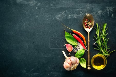 Photo for Herbs and spices with old metal spoon on slate background - Royalty Free Image